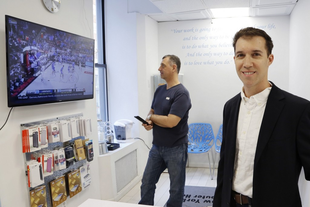 In this March 9, 2016, photo, Joe Silverman, right, poses in the lobby of his New York computer repair shop while employee Alex Lokshin watches the company's big-screen TV. Silverman realized last year he was losing productivity to the NCAA college basketball tournament, as the 20 staffers of his computer repair company kept checking their phones for scores during the games. His solution was to allow them to have the games on the big-screen TV he had installed for customers, but to let them know they do need to focus on their tasks at hand. Silverman keeps an eye on the games, too. (AP Photo/Mark Lennihan)