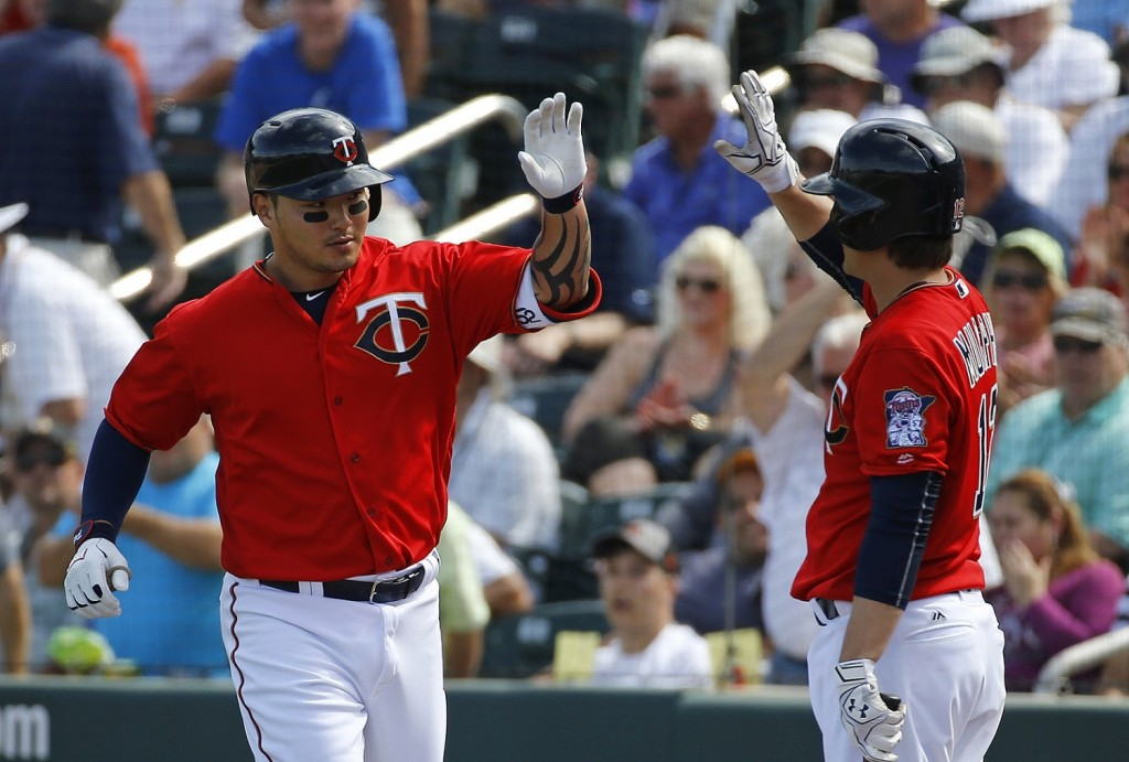 Minnesota Twins' Byung Ho Park, left, of South Korea, high-fives teammate John Ryan Murphy after hitting a solo home run in the fourth inning of a spring training interleague baseball game against the Miami Marlins in Fort Myers, Fla., Friday, March 11, 2016. (AP Photo/Patrick Semansky)