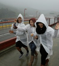 Three women run and laugh in the rain as they begin to cross the Golden Gate Bridge Thursday, March 10, 2016, in Sausalito, Calif. The ongoing deluge of storms in Northern California has swelled lakes and dams, boosting the prospects for outdoor recreation but likely falling short of ending the drought. Heavy rain hit the region north of San Francisco on Thursday with four inches expected by Friday, the National Weather Service said.(AP Photo/Eric Risberg)