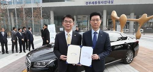 Minister of Land, Infrastructure and Transport Kang Ho-in (L) gives South Korea's first license for self-driving car to a Hyundai Motor executive in a ceremony in the Sejong Government Complex on March 7, 2016. (Yonhap)