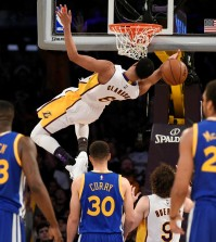 Los Angeles Lakers guard Jordan Clarkson, top, falls from the rim after a dunk during the second half of an NBA basketball game against the Golden State Warriors in Los Angeles, Sunday, March 6, 2016. The Los Angeles Lakers won 112-95. (AP Photo/Kelvin Kuo)