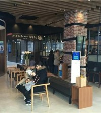 Two customers talk to each other while waiting to handle their financial transactions in a Woori Bank outlet which opened a 'cafe in branch' in Yongsan, central Seoul, on March 28, 2016 in this photo provided by the bank. (Yonhap)