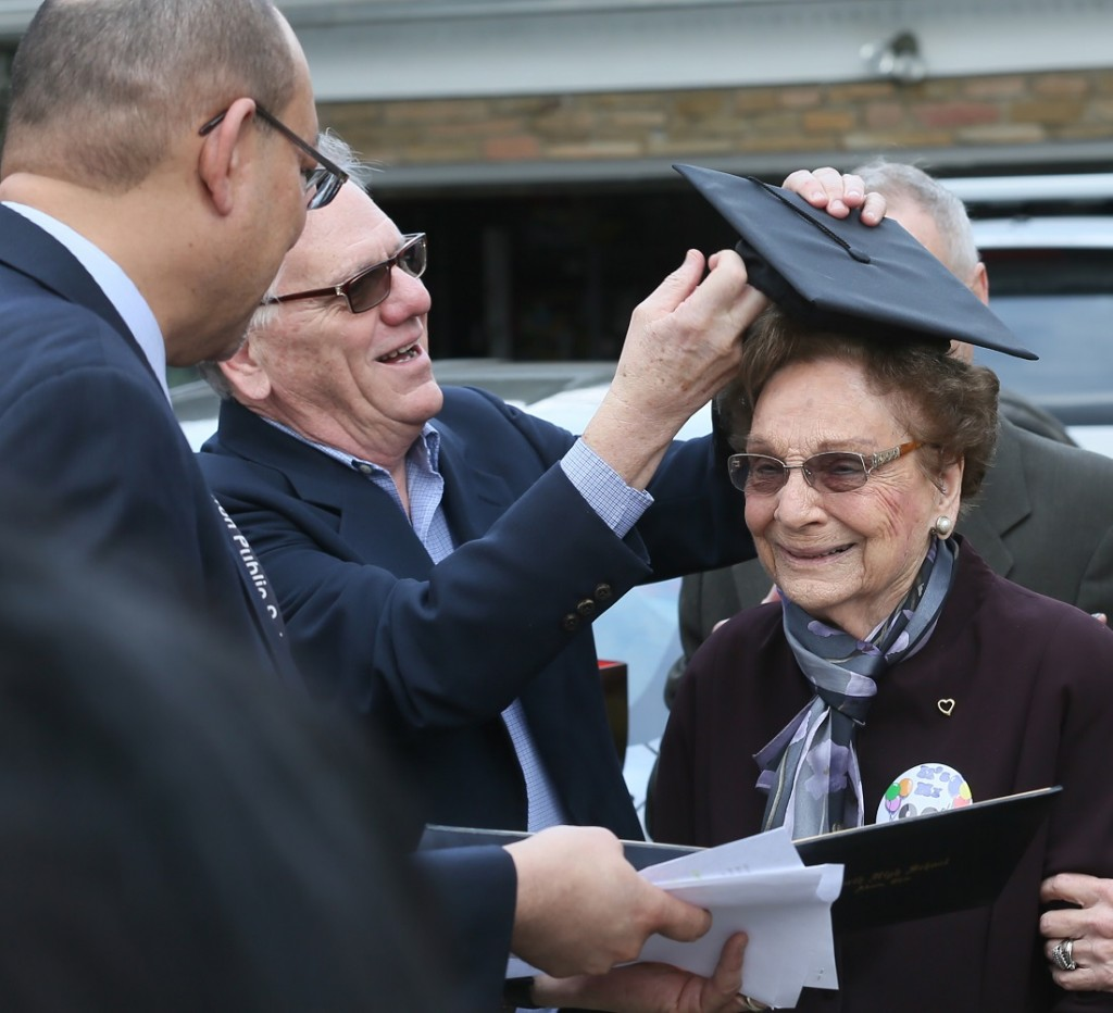 Donald Huston, center, puts a graduation cap on his mother, Dorothy L. Liggett as Akron Schools Superintendent David James, left, presents her belated North High School diploma on Wednesday, March 9, 2016, in Fairlawn, Ohio. Liggett was a few weeks from graduation from Akron's North High School in 1942 when officials discovered she was married. Liggett and her late husband, John Huston, ran away to Kentucky to get married after her husband was called into the U.S. Army Air Corps during World War II. (Michael Chritton/Akron Beacon Journal via AP)