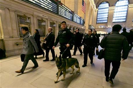 FILE - In this March 22, 2016 file photo, Metro-North Railroad police officers with a police dog patrol Grand Central Terminal, in New York. The best line of defense against a Brussels-style attack in the nation's largest subway system may be man's best friend. The NYPD this week graduated eight new dogs specifically for its elite counterterrorism unit. (AP Photo/Richard Drew)