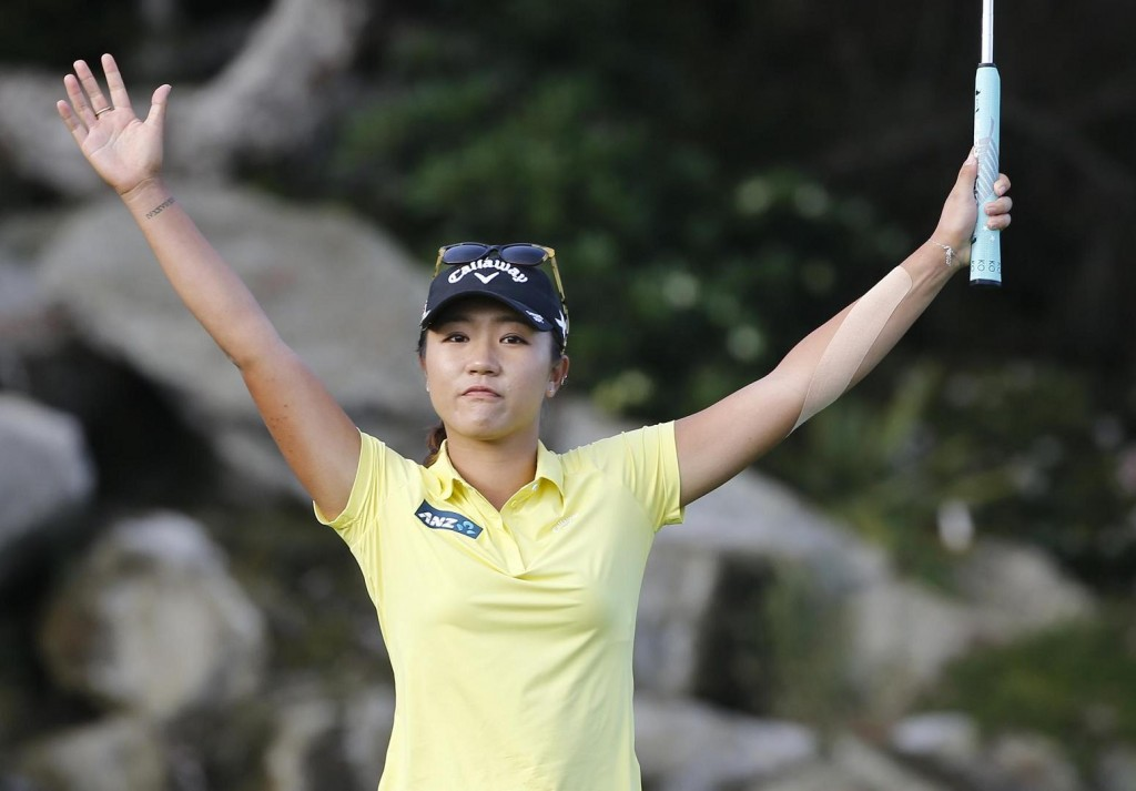 Lydia Ko, from New Zealand, raises her arms in celebration after making a birdie on the final hole to finish 19-under-par and a four shot victory at the Kia Classic women's golf tournament Sunday, March 27, 2016, in Carlsbad, Calif. (AP Photo/Lenny Ignelzi)