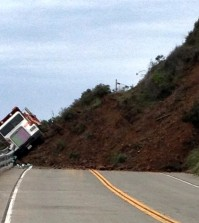 This photo provided by the California Department of Transportation shows a Caltrans dump truck that was nearly toppled by a mud slide along California Highway 1 in Mendocino County, Calif. on Friday, March 11, 2016. The highway is closed indefinitely after the overnight slides. (California Department of Transportation via AP)