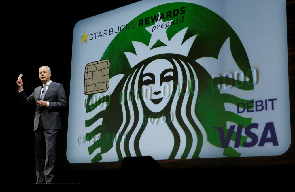 Kevin Johnson, president and chief operating officer of Starbucks Corp., holds up one of the coffee company's new prepaid Visa debit cards, Wednesday, March 23, 2016, at the coffee company's annual shareholders meeting in Seattle. The card can be pre-loaded with money and used for purchases anywhere Visa is accepted, earning the user Starbucks rewards, which can be used to buy Starbucks products. (AP Photo/Ted S. Warren)