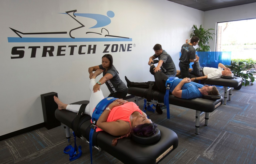 In this March 17, 2016 photo, stretching techniques are demonstrated in at Stretch Zone in Boca Raton, Fla. Some chiropractors and trainers say they're treating more injured clients as the high intensity interval training and hybrid-workout movement has exploded. Most CrossFit and similar high intensity workouts are not meant for average gym-goers, said Jorden Gold, who founded Stretch Zone. During the 30-minute sessions, therapists use bolsters and belts to stretch clients on a table from angles that are nearly impossible to stretch on one's own. (AP Photo/Wilfredo Lee)
