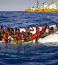 In this photo taken on Sunday, April 17, 2016 migrants ask for help from a dinghy boat as they are approached by the SOS Mediterranee's ship Aquarius, background, off the coast of the Italian island of Lampedusa. The European Union's border agency says the number of migrants crossing the Mediterranean Sea to Italy more than doubled last month. Frontex said in a statement on Monday that almost 9,600 migrants attempted the crossing, one of the most perilous sea voyages for people seeking sanctuary or jobs in Europe.