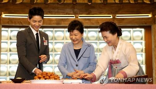 """President Park Geun-hye (C) learns how to make Korean traditional dessert cakes with Song Joong-ki (L), the actor of the hit drama """"Descendants of the Sun,"""" and Yoon Suk-ja, the chief of the Korean Food Foundation, during the opening ceremony of the """"K-Style Hub"""" in Seoul on April 11, 2016. (Yonhap)"""