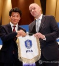 FIFA President Gianni Infantino (R) and Korea Football Association (KFA) President Chung Mong-gyu hold the KFA pennant during a press conference in Seoul on April 27, 2016.
