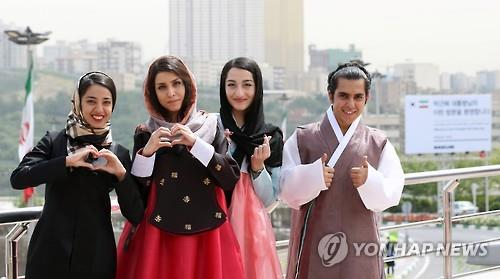 Iranians wearing the Korean traditional dress hanbok make a heart shape with their hands during the Korea Culture Week in Tehran, Iran, on May 2, 2016. (Yonhap).