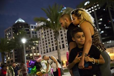 Jennifer Johnson, right, leans on her boyfriend Jeansem Sambolin while standing with her son Tyrone Clarke, 8, as they visit a makeshift memorial for the victims of the mass shooting at the Pulse Orlando nightclub Tuesday, June 14, 2016, in Orlando, Fla. Franky Jimmy Dejesus Velazquez was one of those killed and had worked with Johnson.