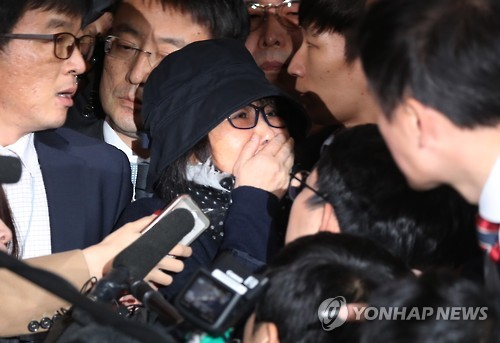 Choi Soon-sil, the woman at the center of South Korea's political scandal, is surrounded by reporters as she enters the Seoul Central District Prosecutors' Office for questioning on Oct. 31, 2016.