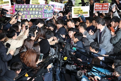 Choi Soon-sil, who is suspected of having meddled in state affairs and peddled influence on various state projects by exploiting her decades-long friendship with President Park Geun-hye, passes through a huge group of reporters to enter the Seoul Central District Prosecutors' Office in Seoul for questioning on Oct. 31, 2016.