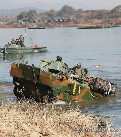 In this photo taken on Nov. 2, 2016, and provided by the Army, an armored combat vehicle crosses a river in Yeoju, 105 kilometers south of Seoul, during a river-crossing exercise.