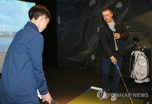 Jordan Spieth (R), the world No. 5 in men's golf, works with a South Korean junior golfer during a clinic at the Under Armour store in Seoul on Jan. 19, 2017.