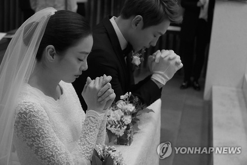 In this photo provided by the Rain Company, singer-actor Rain and actress Kim Tae-hee pray during their wedding at Gahoe-dong Church in central Seoul on Jan. 19, 2017.