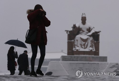 "People walk across Gwanghwamun Square in central Seoul as heavy snow fell across the nation on Jan. 20, 2017, the day of ""daehan,"" one of the 24 seasonal divisions under the lunar calendar that marks the coldest day of the year."