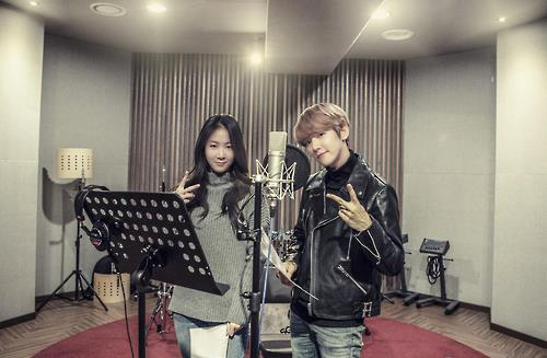 "This undated photo provided by Starship Entertainment shows singers Soyou (L) and Baekhyun posing for the camera at a recording studio for their duet song ""Rain."""