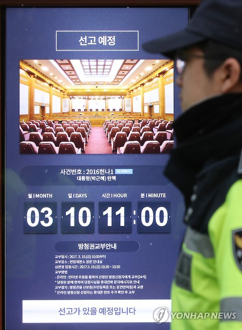 This photo, taken on March 8, 2017, shows a police officer standing next to a notice posted at the entrance to the Constitutional Court in Seoul about a ruling on the impeachment of President Park Geun-hye that the court will make at 11:00 a.m. on March 10. The announcement will be broadcast live from the main courtroom.