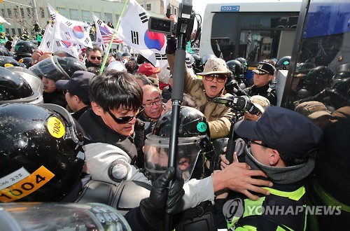 Protesters from conservative civic bodies scuffle with police at an intersection leading to the Constitutional Court in Seoul on March 10, 2017, after the court upheld the impeachment of the president. The ruling, which was announced by the court's acting chief and televised live, made Park the nation's first democratically elected leader to be ousted.