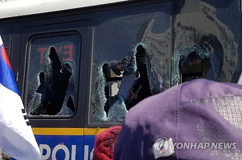 A police bus near the Constitutional Court in central Seoul is damaged on March 10, 2017, as Park Geun-hye supporters clash with police on their way to the court after it ruled to remove Park from her post as the country's president.