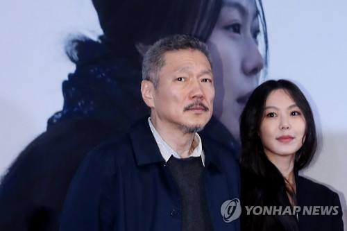 "Hong Sang-soo (L), director of ""On the Beach at Night Alone,"" and its lead actress Kim Min-hee pose for photos during a news conference for the film at a Seoul theater on March 13, 2017."