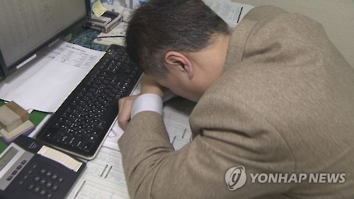 This photo, provided by Yonhap News TV, shows an office worker taking a nap at his office.