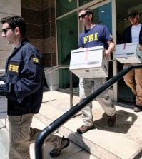 Federal agents carried out boxes of evidence after a raid this month on a California business accused of helping wealthy Chinese investors fraudulently obtain green cards. Credit Richard Vogel/Associated Press