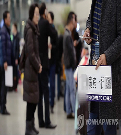 A tour guide waits for Chinese group travelers with a welcome sign in his hand at Incheon International Airport, west of Seoul, on March 3, 2017. (Yonhap)