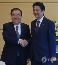 South Korean President Moon Jae-in's special envoy, Moon Hee-sang (L), shakes hands with Japanese Prime Minister Shinzo Abe at the latter's residence in Tokyo on May 18, 2017. (Yonhap)