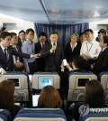 South Korean President Moon Jae-in (holding a mic) speaks to reporters while aboard Air Force One en route to Washington on June 28, 2017, for his summit with U.S. President Donald Trump later in the week. (Yonhap)