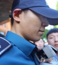 South Korean singer and actor T.O.P. of boy band BIGBANG, who is serving his mandatory military service as a conscripted policeman, leaves his workplace in Seoul surrounded by reporters questioning his marijuana charges on June, 5, 2017. (Yonhap)