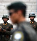 Two North Korean soldiers looking at a South Korean soldier, center, standing guard at the border village of Panmunjom. Credit Lee Jin-Man/Associated Press