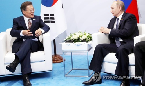 South Korean President Moon Jae-in (L) and Russian President Vladimir Putin hold bilateral talks on the sidelines of the G20 summit in Hamburg, Germany, on July 7, 2017. (Yonhap)