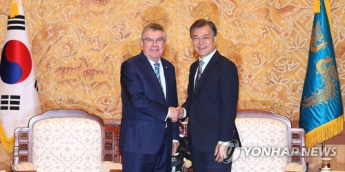 South Korea's President Moon Jae-in and International Olympic Committee Chief Thomas Bach shake hands at the South Korean presidential office Cheong Wa Dae in Seoul on July 3, 2017. (Yonhap)