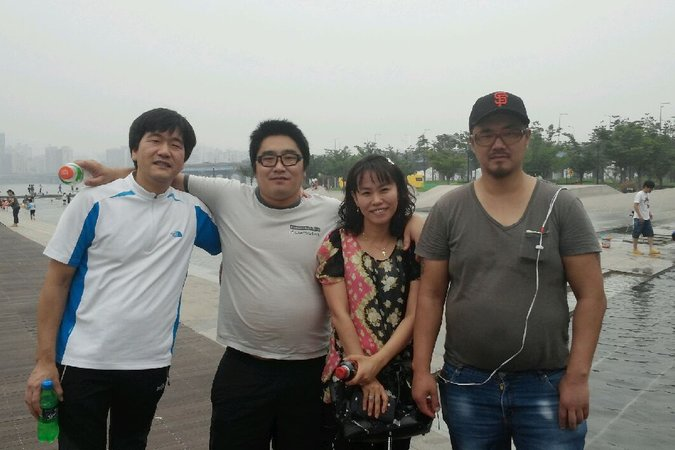 Phillip Clay, right, in a park on the Han River in Seoul, with a female social worker, a fellow deported adoptee and Song Pil-heung, left, who worked at the emergency home where Mr. Clay lived in 2014. Credit Song Pil-heung