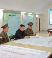 A photo released on Tuesday by North Korea's state news agency purporting to show Kim Jong-un at a military command center. The screen at right shows an American base on Guam; some of the maps were digitally blurred by the agency before distribution. Credit Korean Central News Agency, via Reuters