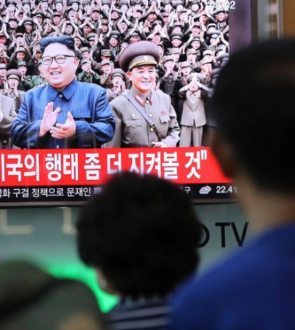 A handful of people paused at a train station in Seoul on Tuesday to watch coverage of North Korea's threats to launch missiles into waters near Guam. Credit Lee Jin-Man/Associated Press