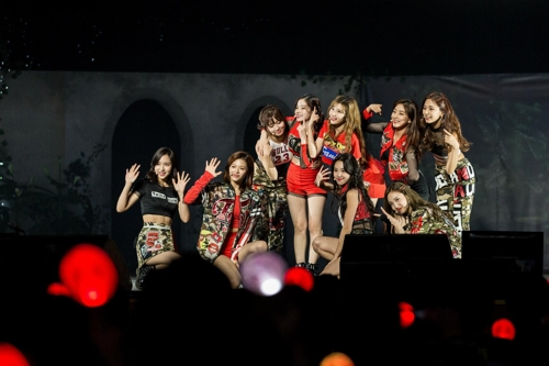 This photo provided by JYP Entertainment shows girl group TWICE waving to fans on stage during a two-day meet-and-greet event marking its two-year debut anniversary at Kyunghee University in Seoul held Oct. 14-15. (Yonhap)