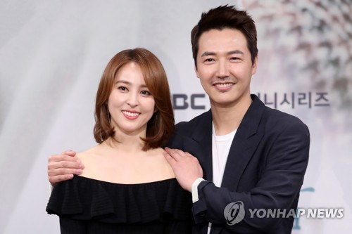 "Han Hye-jin (L) and Yoon Sang-hyun (R) pose for photos during a media event for their new TV series ""Let's Look at the Sunset Holding Hands"" held at the network's headquarters in Sangam-dong, western Seoul, on March 20, 2018. (Yonhap)"