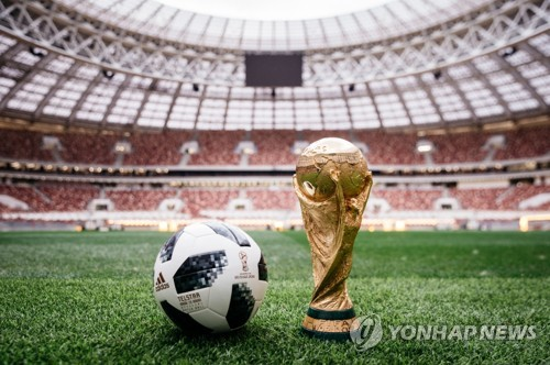 This photo, provided by Adidas, shows Telstar 18, the official match ball of the 2018 FIFA World Cup in Russia, and the FIFA World Cup trophy. (Yonhap)