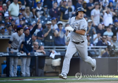 In this Getty Images photo, Choi Ji-man of the Milwaukee Brewers looks back as he scores during the top of the 12th inning against the San Diego Padres at Petco Park on March 29, 2018, in San Diego, California. (Yonhap)