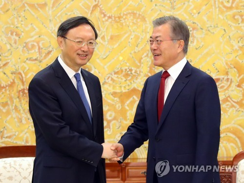 South Korean President Moon Jae-in (R) shakes hands with Chinese State Councilor Yang Jiechi before the start of their meeting at the presidential office Cheong Wa Dae in Seoul on March 30, 2018. (Yonhap)