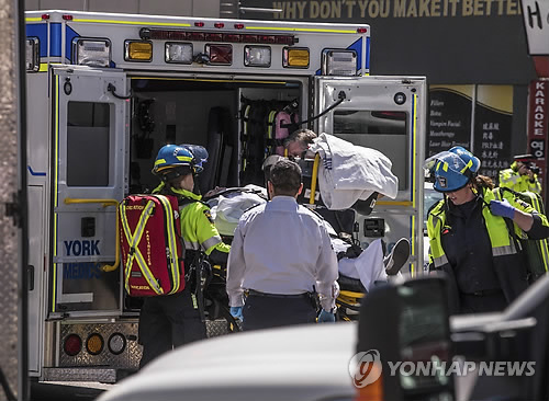 This photo released by the Associated Press shows rescue workers transporting an injured person into an ambulance in Toronto after a van mounted a sidewalk and crashed into pedestrians on April 23, 2018. (Yonhap)