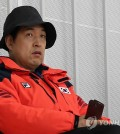 In this file photo from Feb. 17, 2014, Jun Myung-kyu, then vice president of the Korea Skating Union, watches the national speed skating team's practice during the Sochi Winter Olympics at Adler Arena in Sochi, Russia. (Yonhap)
