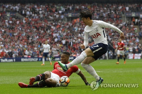 This photo taken by the Associated Press shows Tottenham Hotspur's Son Heung-min (R) trying to take a shot as Manchester United's Antonio Valencia tackles during the English FA Cup semifinal match between Manchester United and Tottenham Hotspur at Wembley Stadium in London on April 21, 2018. (Yonhap)