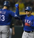In this Getty Images photo, Choo Shin-soo of the Texas Rangers (R) is congratulated by Joey Gallo after hitting a solo home run against the Oakland Athletics in the top of the ninth inning of their major league regular season game at Oakland Coliseum in Oakland on April 4, 2018. (Yonhap)