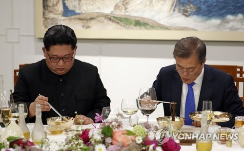 President Moon Jae-in (R) and North Korean leader Kim Jong-un eat Pyongyang naengmyeon during their summit dinner on April 27, 2018. (Yonhap)